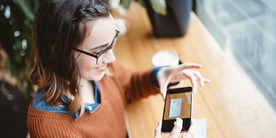 woman using smartphone to deposit check through banking app