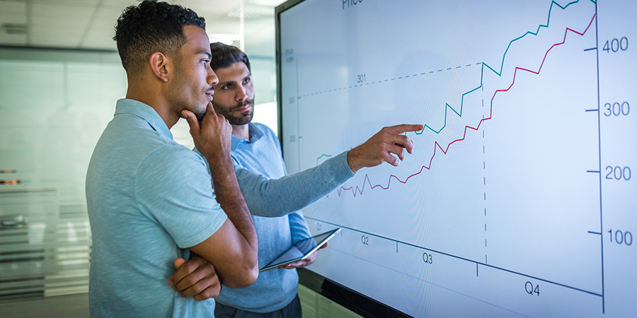Two men looking at a chart on a large monitor