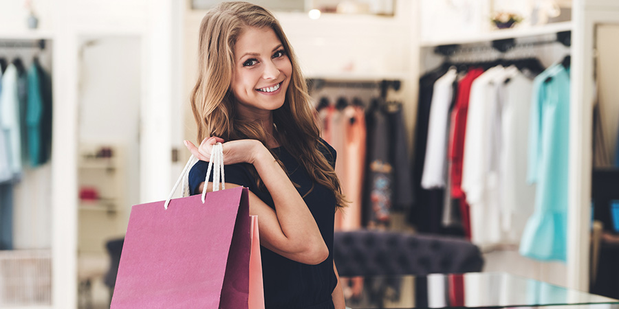 woman holding shopping bags in clothing store