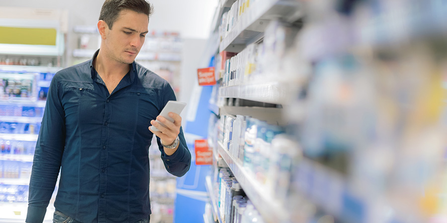 man using smartphone in store